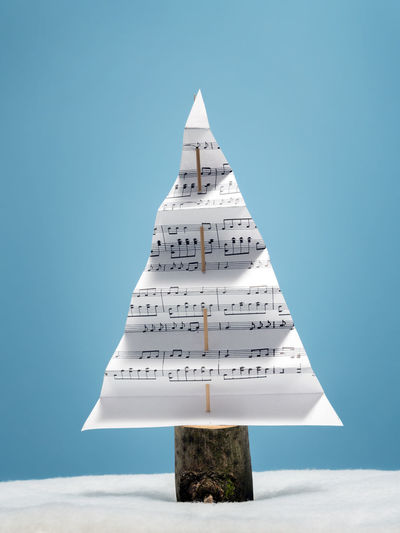 Paper christmas tree with christmas carol notes over light blue background Christmas Carol Christmas Decoration Christmas Tree Decoration Holidays Music No People Note Paper Triangle Shape White