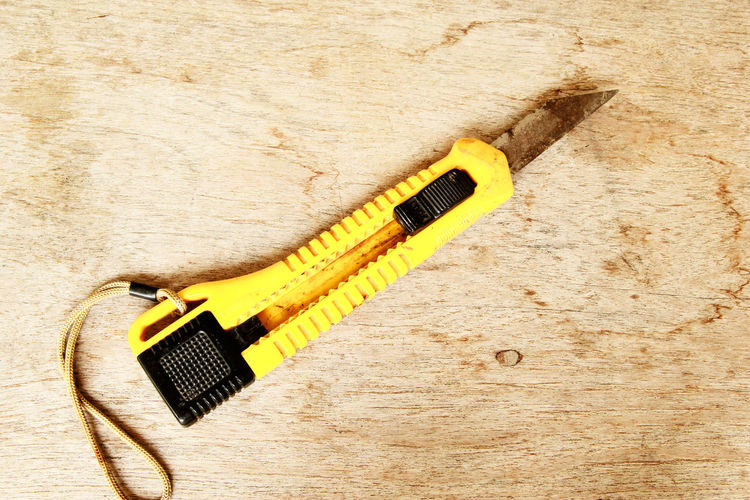 Close-up of utility knife on wooden table