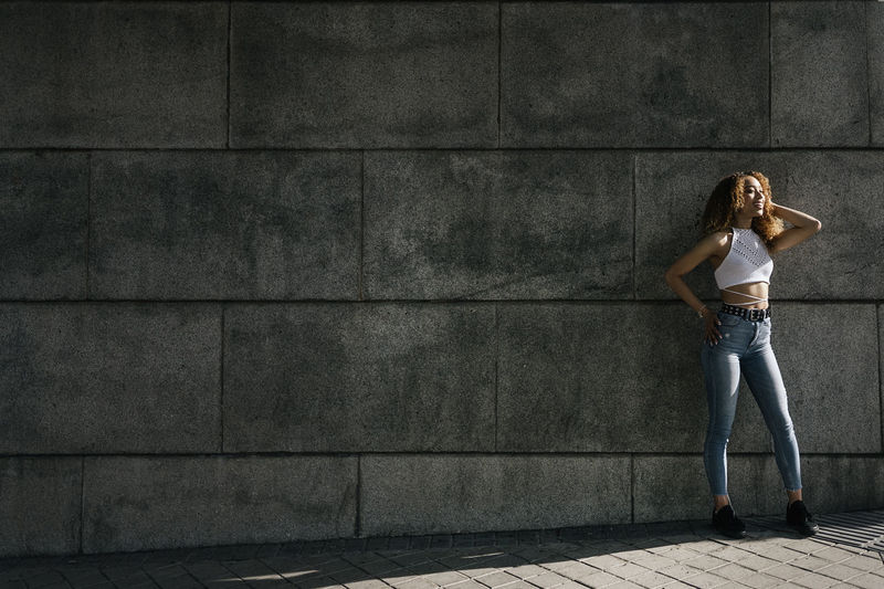 Full length of woman standing by concrete wall