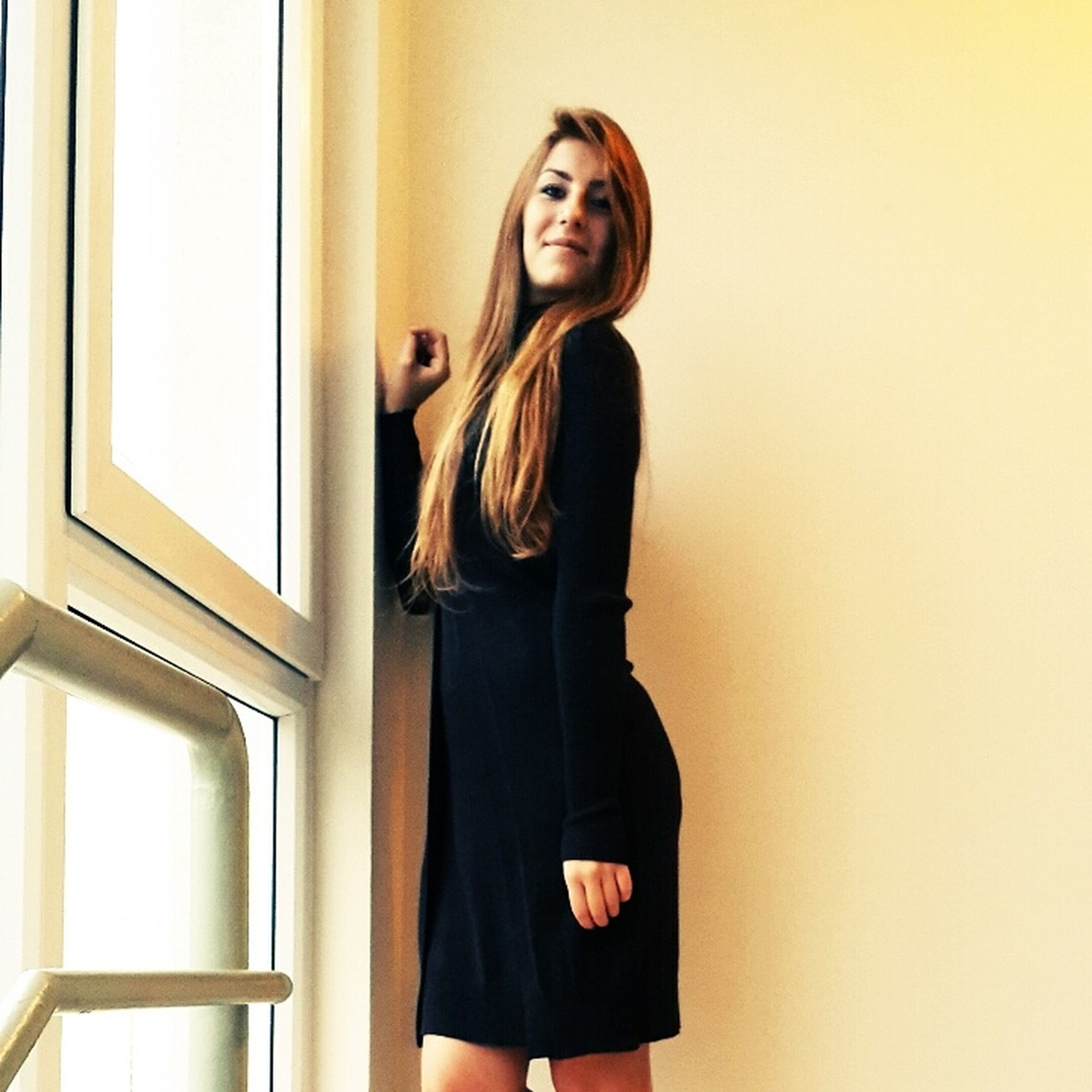 young adult, young women, standing, lifestyles, long hair, indoors, front view, three quarter length, person, casual clothing, portrait, looking at camera, leisure activity, wall - building feature, beauty, waist up, sensuality