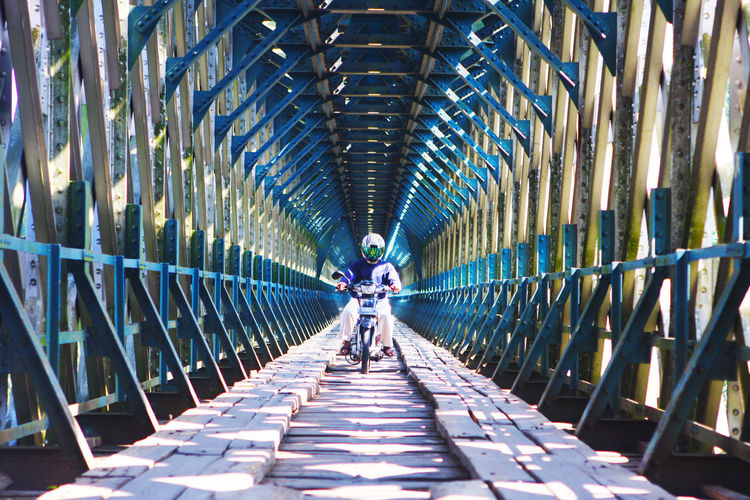 Person Riding Motorcycle On Covered Bridge