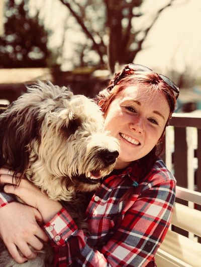 Portrait of smiling young woman holding dog during sunny day