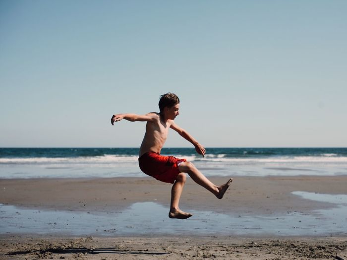 Full Length And Side View Of Boy Jumping On Beach