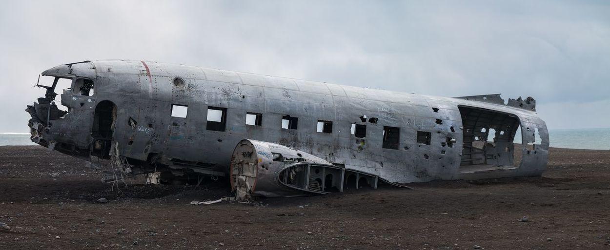 Abandoned airplane on beach against sky