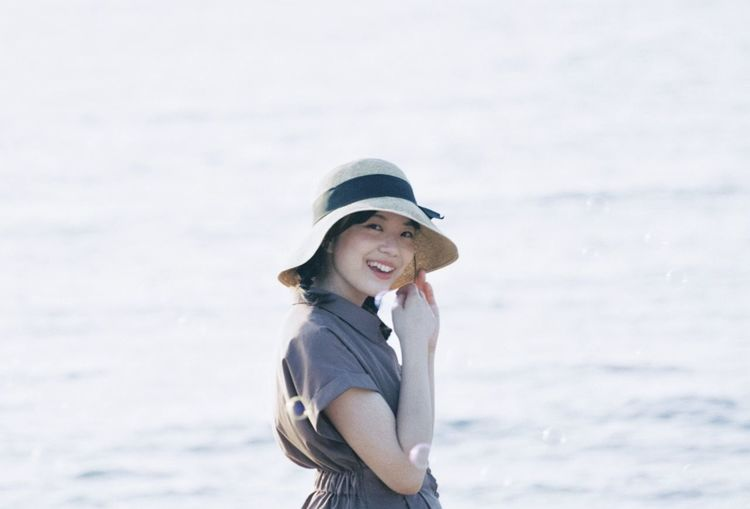 Portrait of a smiling young woman standing on beach