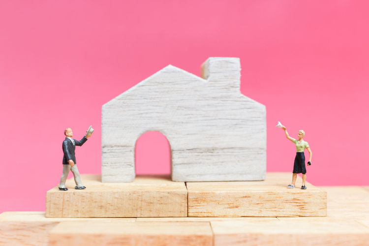 Close-Up Of Figurines With Model Home On Table Against Pink Background