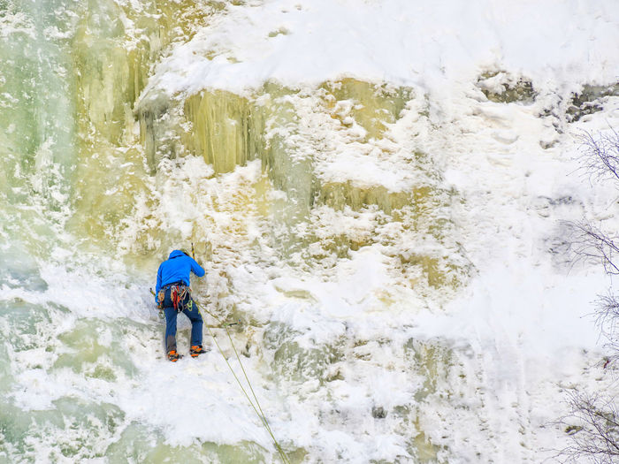 Rear View Of Man Climbing On Frozen Mountain During Winter