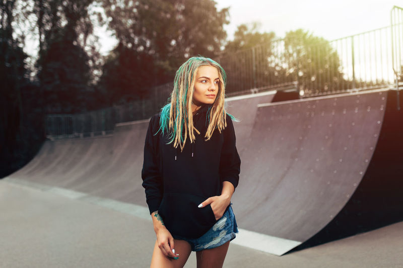 a young girl in denim shorts and a black hoodie with dreadlocks. Standing in a skate park EyeEmNewHere Skateboarding Activity Black Casual Clothing Casual Style Clothing Day Dreadlocks Hairstyle Hoodie Leisure Activity Lifestyles One Person Real People Skate Skateboard Park Standing Teenager Three Quarter Length Young Adult Young Women Youth Culture Youth Style
