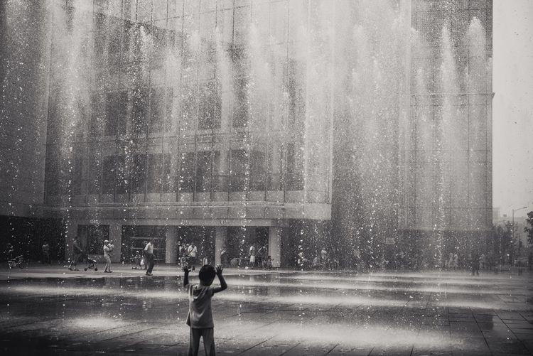 Full length of woman standing on wet city against sky