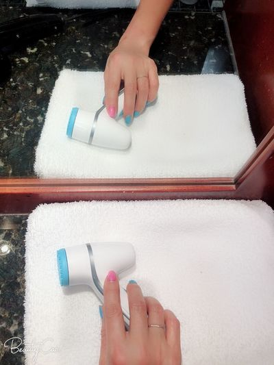 High angle view of woman hand holding hair dryer on towel by mirror