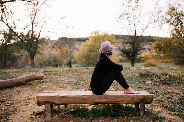 Side view of woman sitting on bench at park