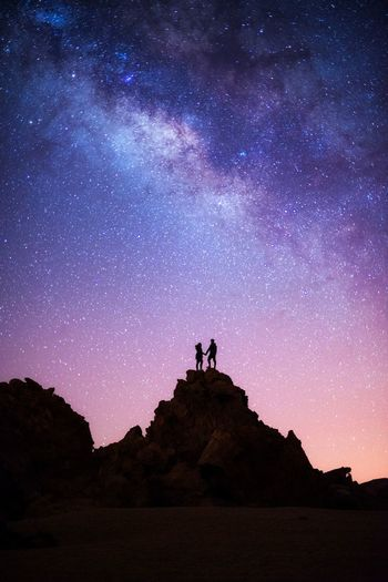 Silhouette couple standing on rock formation against sky at night
