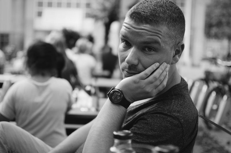 Bored young man with hand on chin sitting at restaurant