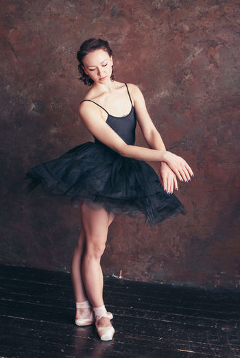 Full length of young woman dancing against wall
