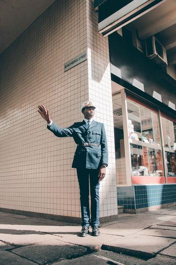Full length of man standing against building in city