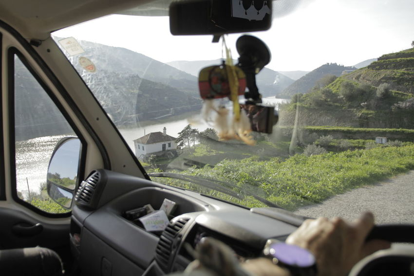 Looking through windscreen at mountain path and river Car Car Interior Close-up Day Human Hand Land Vehicle Landscape Men Mode Of Transport Mountain Nature One Person Outdoors Real People Road Sky Transportation Windshield