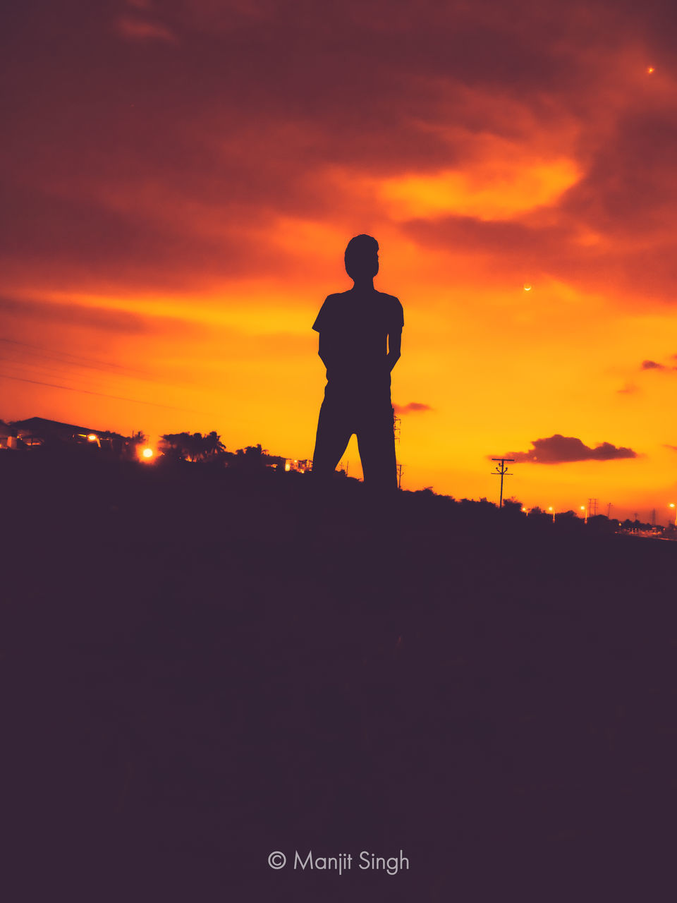 SILHOUETTE MAN STANDING ON FIELD DURING SUNSET