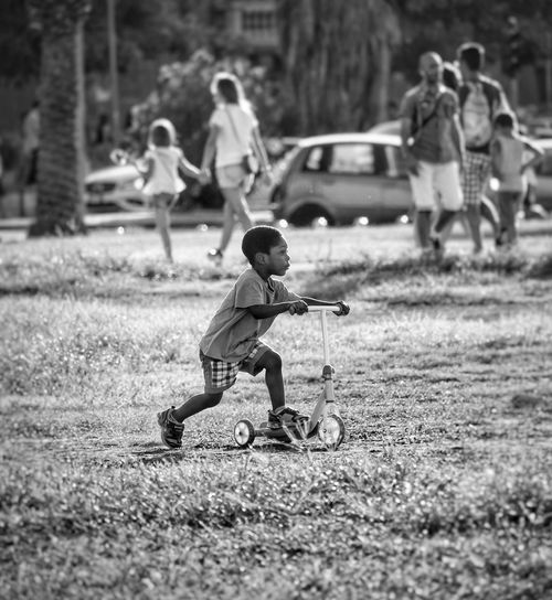 Boy with push scooter on field at park