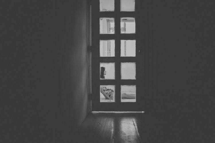 Side view of woman sitting at home seen through closed door