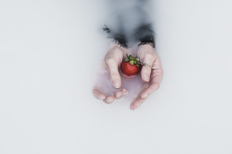 Cropped hand of woman with strawberry in milk