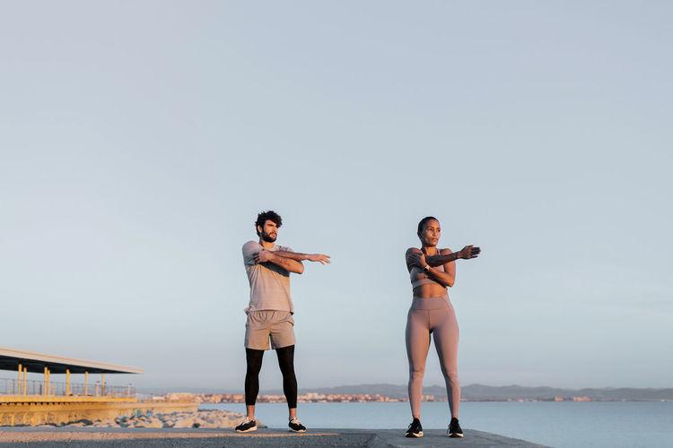 Full length of woman standing on mobile phone against sky