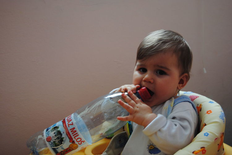 Portrait Of Cute Boy Holding Bottle At Home