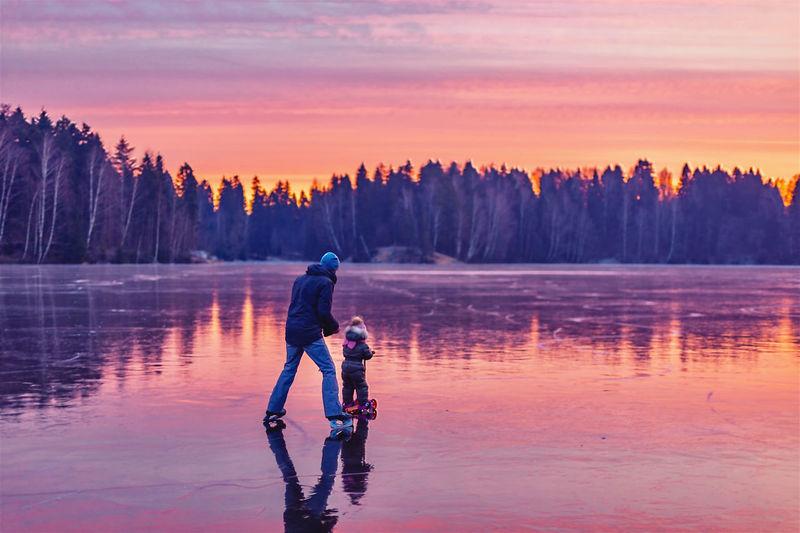 Full length of man on lake against sky during sunset