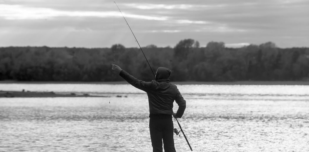 Rear view of man fishing on shore against sky