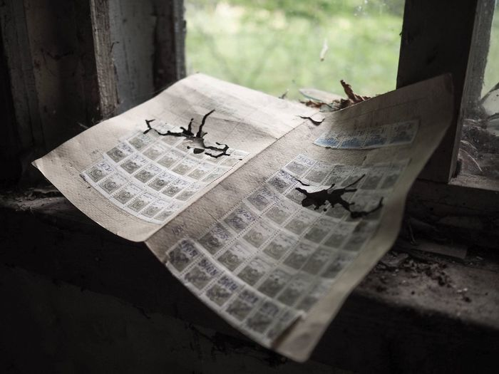Close-up of abandoned postage stamps on window sill
