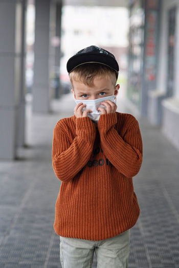 A boy in a cap and an orange sweater holds a medical mask with his hands.
