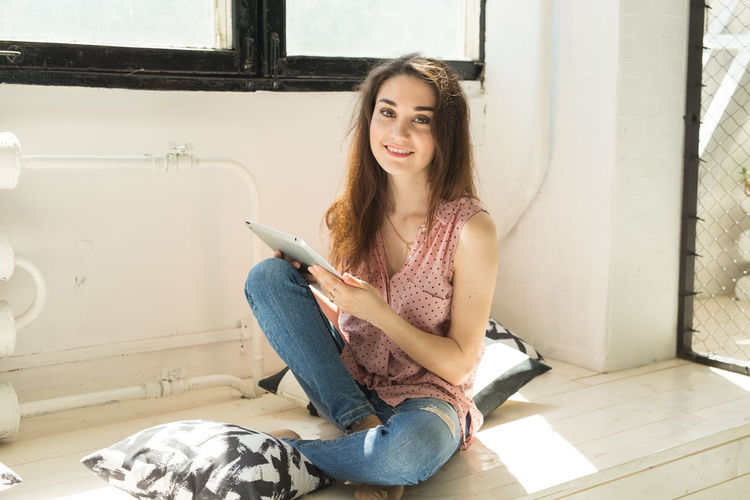 Young woman using phone while sitting on floor at home