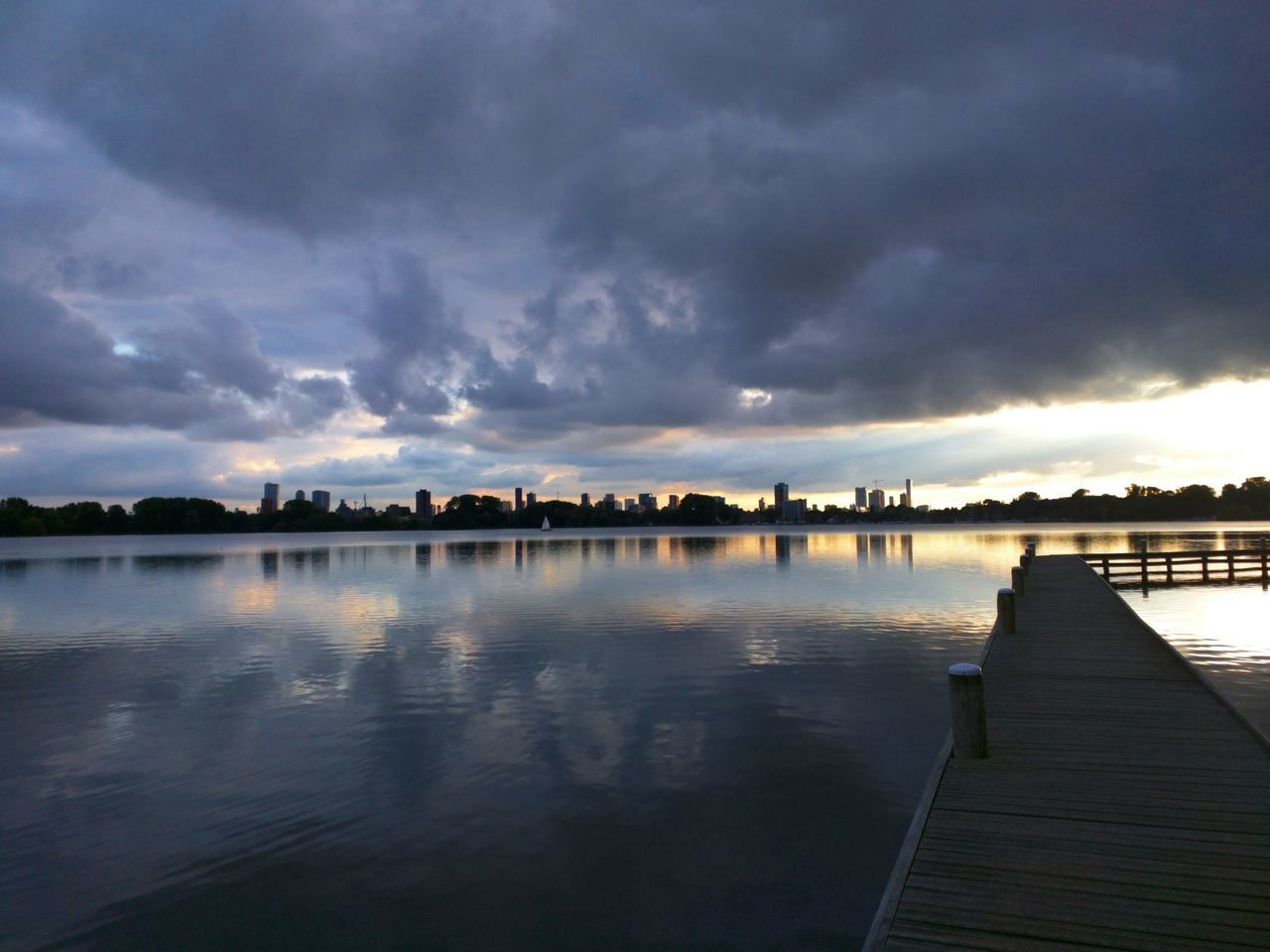 Pier At Calm Lake Against Cloudy Sky During Sunset