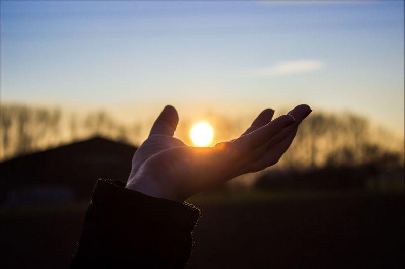 Human hand pretending to hold sun