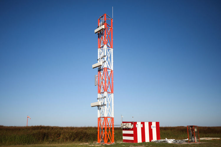Low angle view of communications tower on field against clear sky