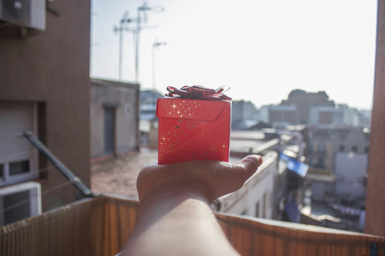 Cropped image of person holding gift box by city against clear sky