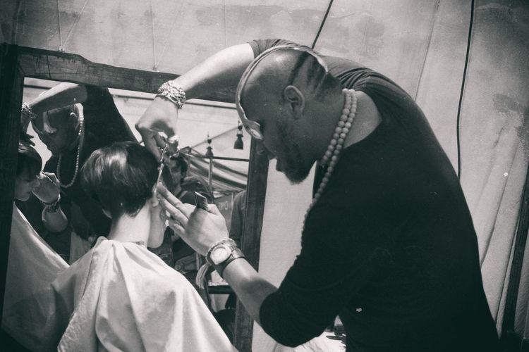 Barber cutting hairs of boy at salon