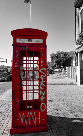 Red telephone booth on sidewalk against sky in city