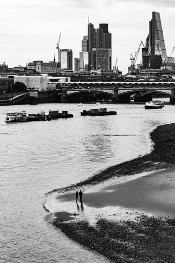 A Couple on Thames River bank in Central London A Couple Blackandwhite Candid Photography Candidmoments Candidshot Cityscape Day London_river Low Tide On Thames Thames