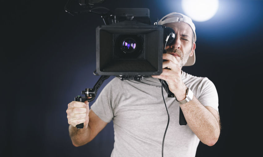 Man holding camera while standing against black background