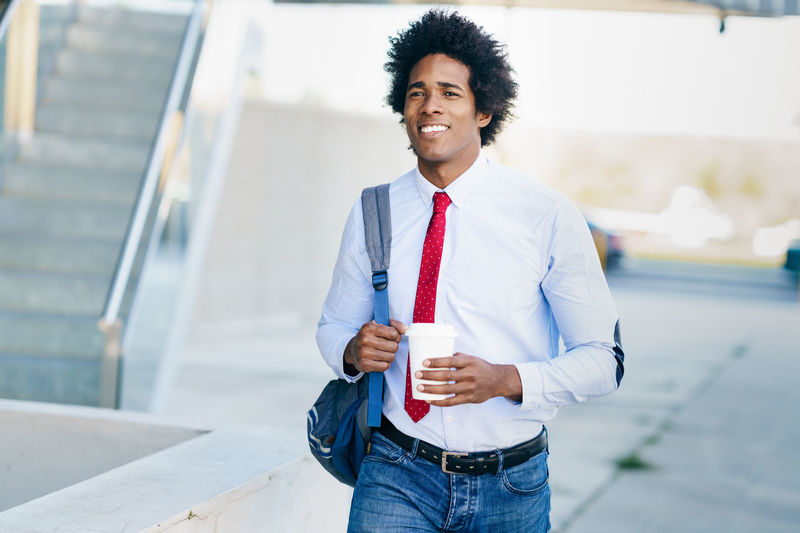 Smiling businessman holding disposable cup while walking