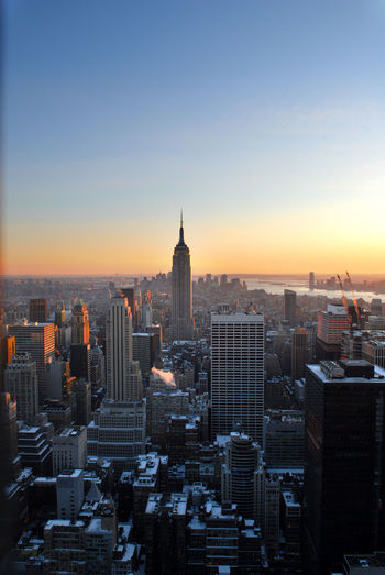 Mid distance of empire state building amidst cityscape against sky during sunset