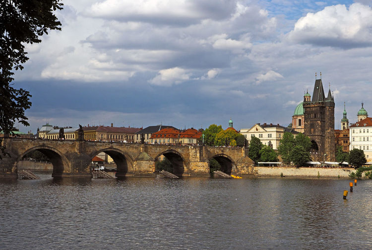 Arch bridge over river by buildings in city against sky