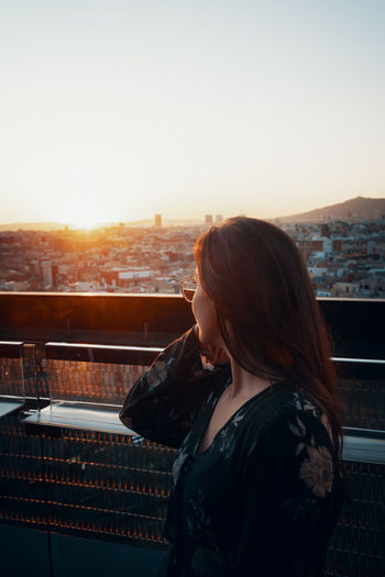Woman looking at city at sunset
