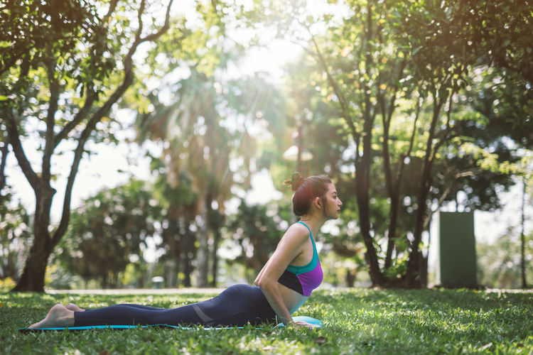 Side View Of Young Woman Exercising At Park
