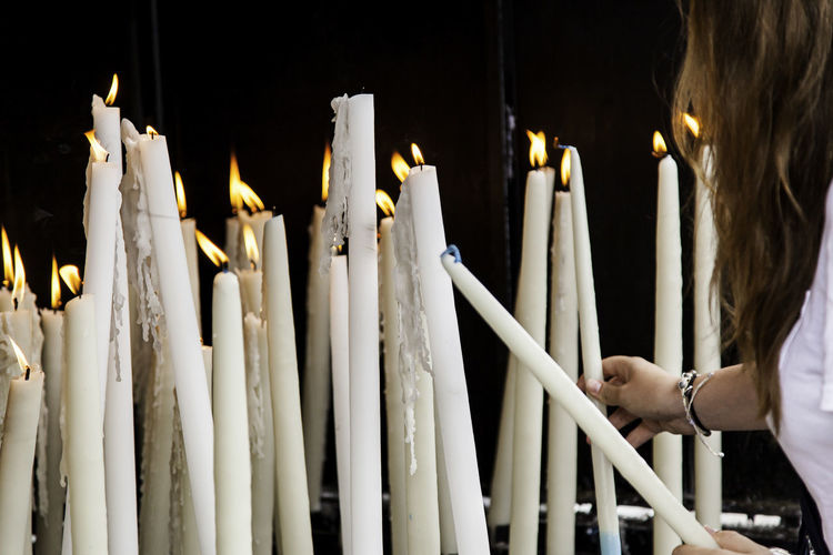 Close-up of woman igniting candle at church
