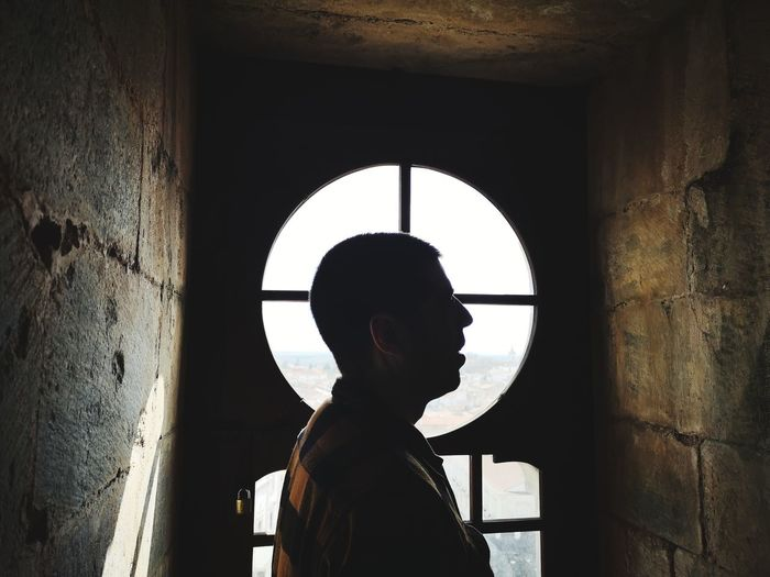 Rear view of man looking through window in building