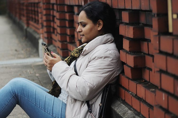 Mid Adult Woman Using Phone On Footpath