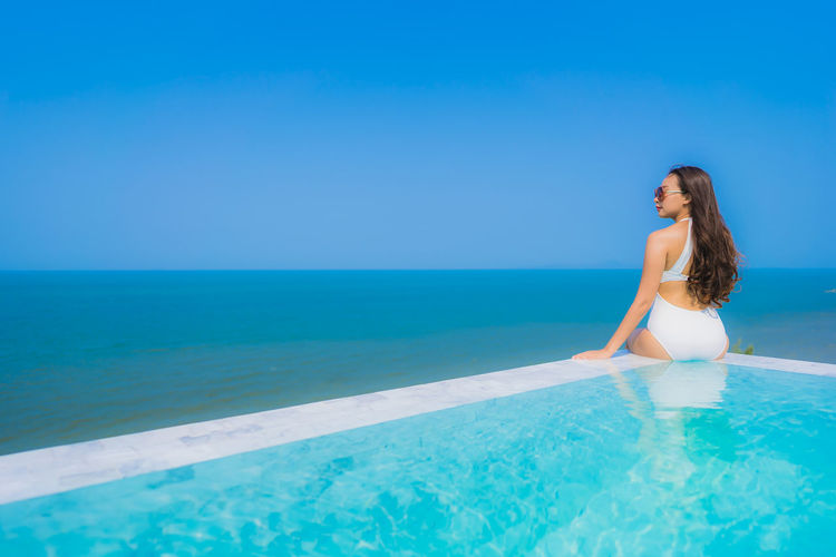 Young woman sitting at infinity pool against sea