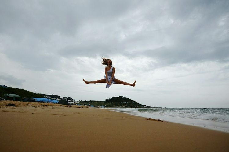 Low angle view of woman doing the splits over beach against cloudy sky
