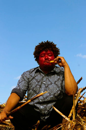 Low angle view of man eating sugarcane against clear sky